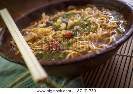 Spicy asian ramen noodle soup with chopsticks in wooden bowl