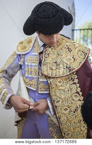 Baeza SPAIN - August 15 2014: Spainish bullfighter Sebastian Castella putting itself the walk cape in the alley before going out to bullfight typical and very ancient tradition in Baeza Jaen province Spain