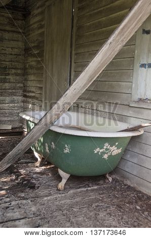 An old claw foot bathtub in an old broken down house.