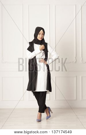 studio photo beautiful young woman of Middle Eastern appearance in the modern Muslim women's dress, high heels and a scarf on her head, on light background classical