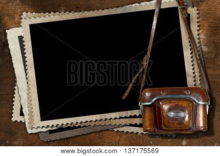 Old and vintage camera with leather case and a stack of old vintage photo frames on a wooden background