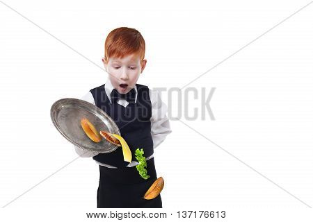 Clumsy little waiter drops food from tray serving hamburger. Cheeseburger falling with separated toppings. Dropping burger layers. Redhead child boy in suit failure, isolated at white background