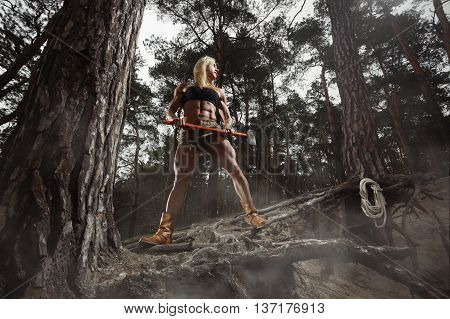 Art fitness. Fitness woman lumberjack. Fitness woman lumberjack holding a huge ax and rope. Fitness woman lumberjack standing on the forest background. Bodybuilder with an ax. Fitness woman with ax