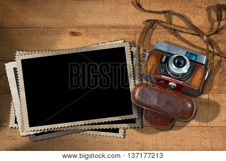 Old and vintage camera with leather case and a stack of old vintage photo frames on a wooden table