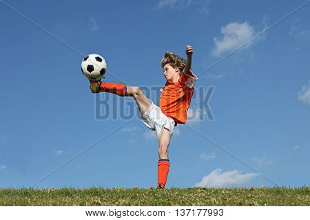 kid playing football or soccer kicking ball