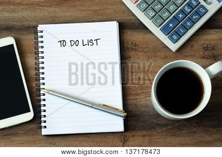 Text to do list on a notepad with smart phone pen coffee and calculator on a wooden table with copy space.