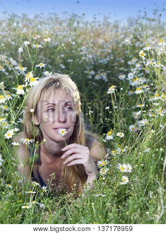 The happy young woman in the field of camomiles
