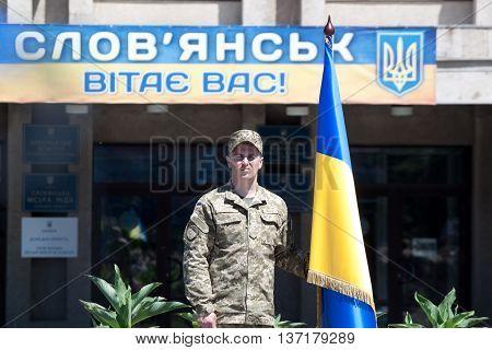 A Soldier Stands Near A Ukrainian Flag