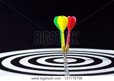 Three Darts On Target. Horizontal Shot With Black Background.