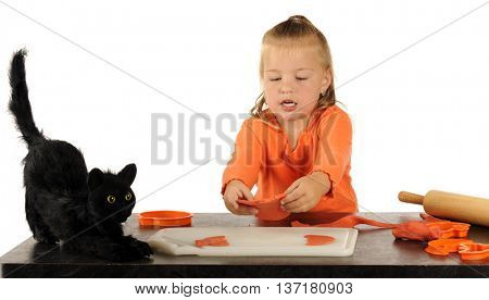 A cute preschooler picking up the pumpkin shape she's just created with a cookie cutter.  A scary black cat sits nearby.