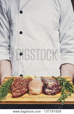 Chef holds fresh steaks ready for BBQ cooking - pork, beef and chicken. Raw meat on a cutting board with rosemary leaf on wood, closeup. Marinated in spices for barbecue.