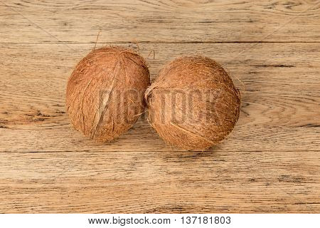 Two whole brown coconut lie side by side on the old oak board
