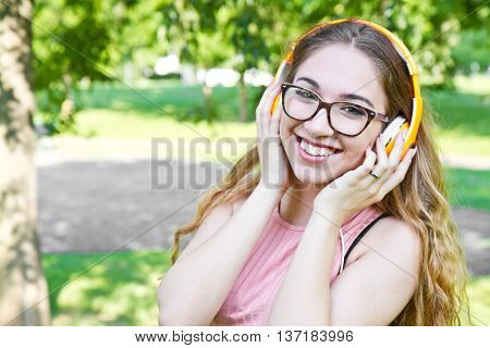 young girl listen music with headphone in the park