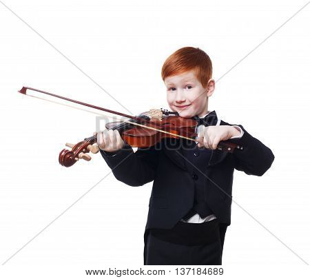 Cute redhead child plays violin isolated at white background. Red-haired charming boy musician in tailcoat or tuxedo. Classical music study concept