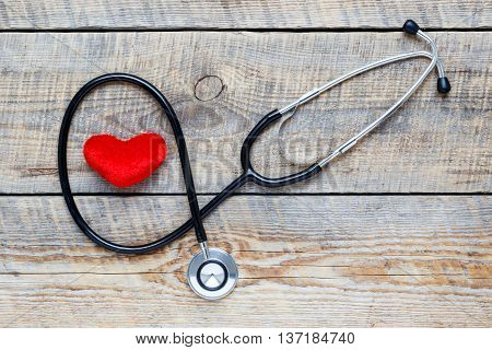 new stethoscope with red plush heart on wooden table close up