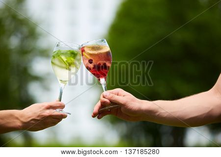 Hand holding glasses of cocktail clinking together at outdoor.