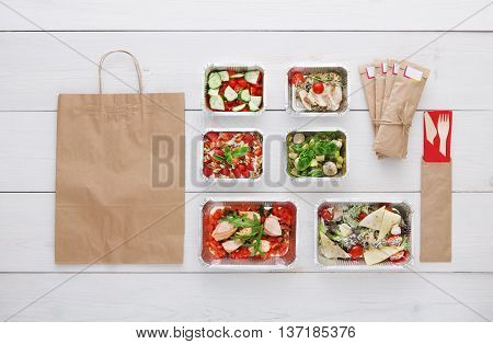 Healthy food delivery. Take away of natural organic low carb diet. Fitness nutrition in foil boxes, water bottle, cutlery and brown paper package with copy space. Top view, flat lay at white wood
