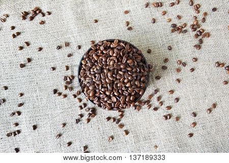 Burlap texture with coffee crop in a bowl background, plenty of robusta beans in plate. Sack cloth canvas with copy space. Scattered seeds at hessian textile