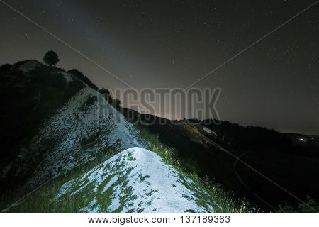 Summer night sky over the white chalky mountains, hills. Starry night landscape. Night background.