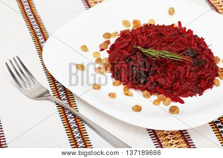 Grated beet salad with prunes and raisins served on a white plate and home tablecloth with fork