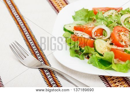 Fresh salad with sliced tomato cucumber onion lettuce seasoned with soy sauce dry spices and sesame. Low aperture shot focus on fork and part of salad