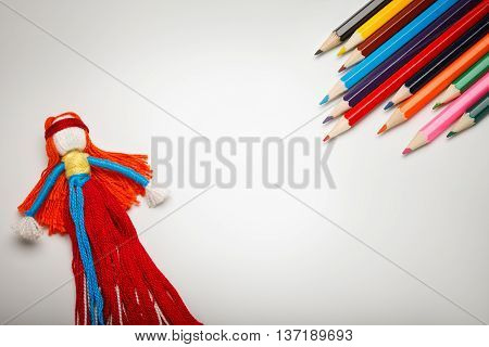 Children`s play background with colorful doll and pencil with empty space in center.
