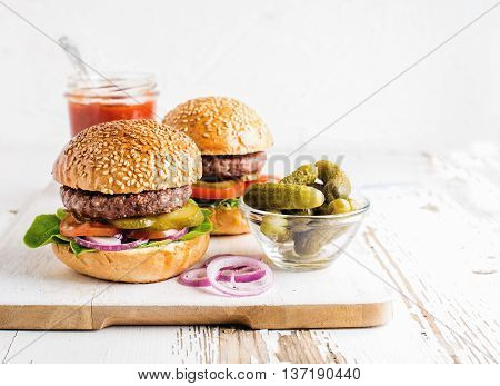 Two fresh homemade burgers, pickles, ketchup and onion rings on white wooden serving board. White background, selective focus, horizontal composition