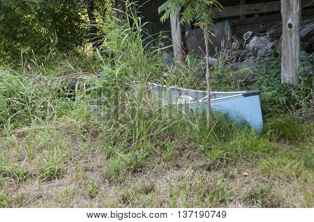 A water filled canoe laying in the weeds next to a falling down shed.