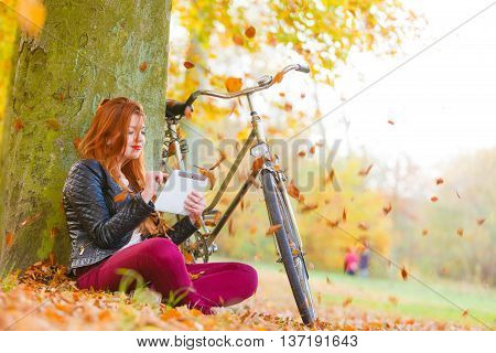Nature outdoors concept. Leaves are surrounding beautiful girl. Young lady is sitting under the tree wearing red trousers.