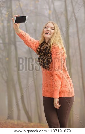 Happy fashion woman in fall autumn park taking selfie self photo picture. Pretty joyful young girl in sweater pullover photographing.