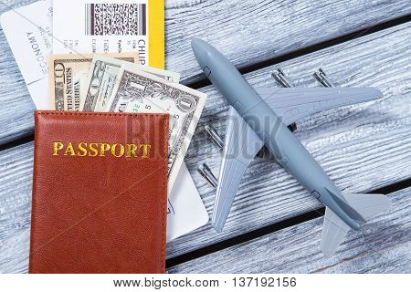 Brown passport and toy plane. Dollar bills on tickets. Document for identification. Money for traveling abroad.
