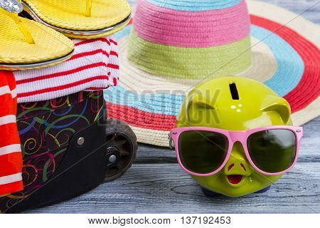 Suitcase near piggy bank. Striped beach hat and clothes. Girl's luggage for summer journey. Wealth, luxury and happiness.