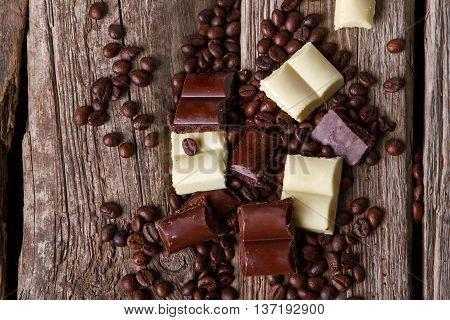 Coffee beans and brown chocolate. Pieces of dark chocolate. Product high in calories. Confectionery of high quality.