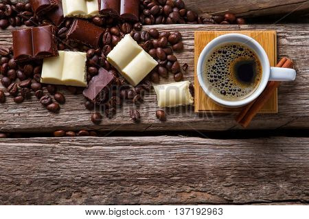 Chocolate near cup with coffee. Top view of coffee cup. Americano and milk chocolate. Aroma that wakes you up.