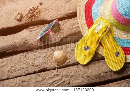 Flips flops and seashells. Woman's beach hat and sunglasses. Relax during your trip. Leave all worries behind.