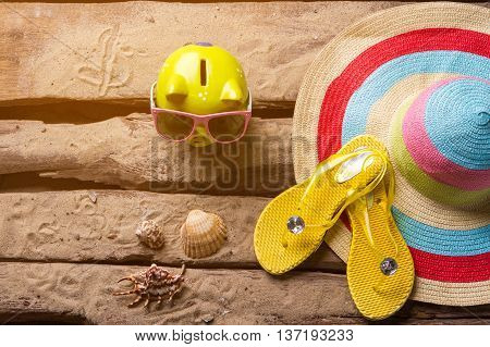 Piggy bank and seashells. Beach hat near money box. Journey to expensive resort. Time to fork out.