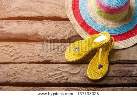 Flip flops near a hat. Beach hat on sand. Take a trip this summer. Rest at the ocean coast .