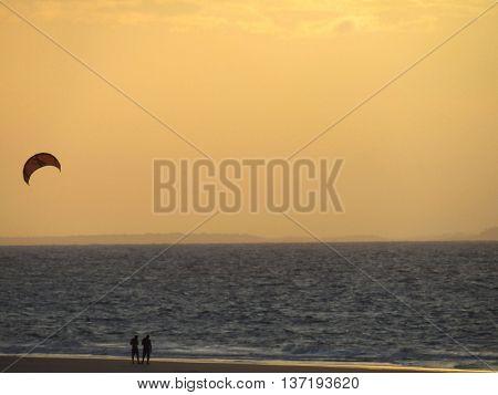 Someone is kitesurfing under the sunset light
