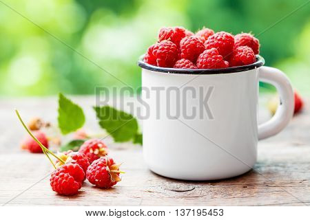 Fresh Raspberries In White Enamelled Mug On Table Outdoors.