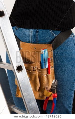Female worker on a ladder with tools in holster