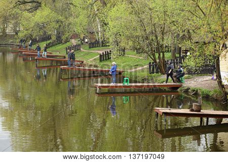 MOSCOW - MAY 03, 2015: Adults and children with a fishing pole sitting on the pier near the pond