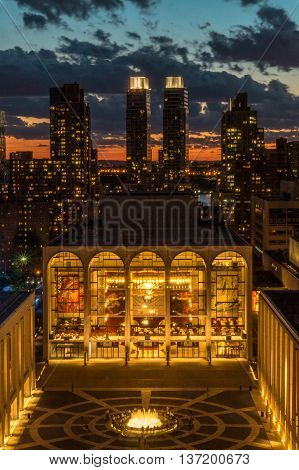 New York NY USA - June 22, 2016: On a pleasant summer's evening visitors came to enjoy the sites at Lincoln Center located on the Upper West Side of Manhattan in New York City. Shown is the fully lit Metropolitan Opera House