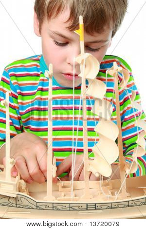 Small boy in striped shirt work with zeal on artificial ship