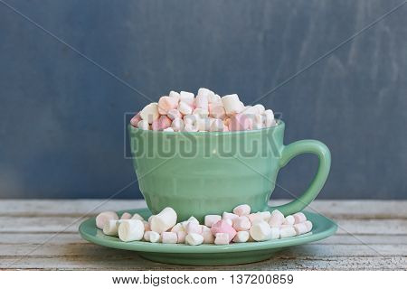 Green Cup and saucer to the top filled with marshmallow