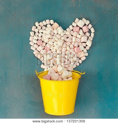 bunch of marshmallow laid out in the shape of a heart over a yellow bucket on blue background