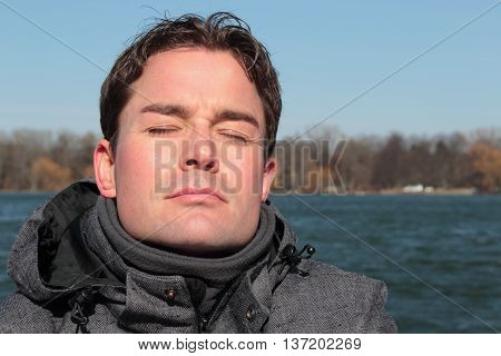 Man relaxing on a lakesite facing the sun eyes closed