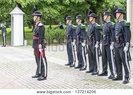 OSLO, NORWAY - JULY 1: Norwegian soldiers in gala uniforms changing honor guard in front of the Royal Palace on July 1, 2016 in Oslo, Norway. This daily ceremony is a big tourist attraction.