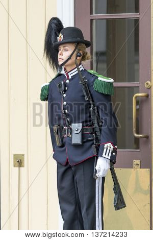 OSLO, NORWAY - JULY 1: Norwegian soldier woman in gala uniforms changing honor guard in front of the Royal Palace on July 1, 2016 in Oslo, Norway. This daily ceremony is a big tourist attraction.