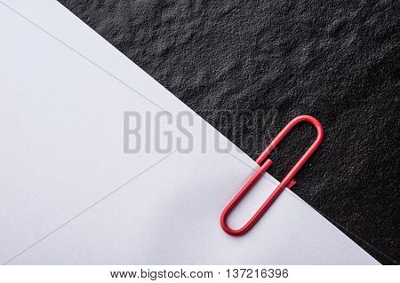 close up of a red paper clip and paper on black background