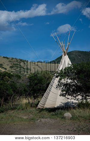 Tepee with streamers flying in the breeze with blue skies